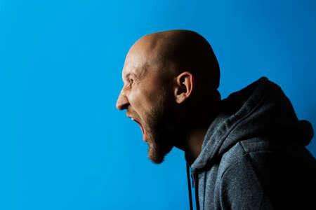 Man screams on a blue background. Concept of aggression, fan, joy.