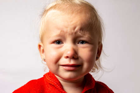 Little baby crying on a light background. The concept of a bad mood, naughty child, teeth grow.
