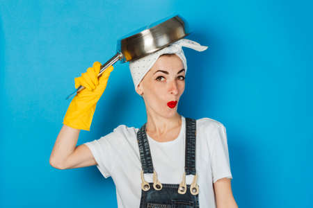 A young girl with a scarf on her head and yellow rubber gloves is holding a pot over her head against a blue background. The concept of cleaning and cleaning service, washing dishes Imagens