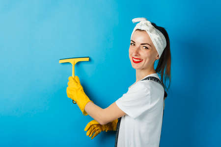 A young girl with a smile and a handkerchief on her head is wiping off the dirt with a shkrebk on a blue background. Cleaning Concept and Cleaning Service