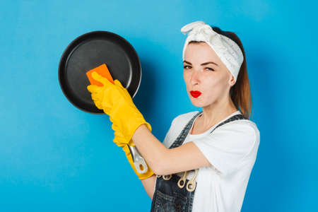 A young girl with a smile and a handkerchief and yellow rubber gloves wipes a frying pan on a blue background. Cleaning Concept and Cleaning Service