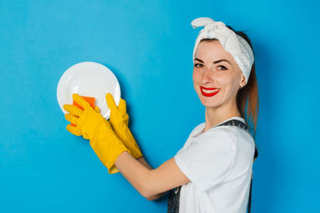 Young girl with a scarf on her head and yellow rubber gloves holds a white plate and a sponge on a blue background. Concept of cleaning and cleaning service, washing dishes