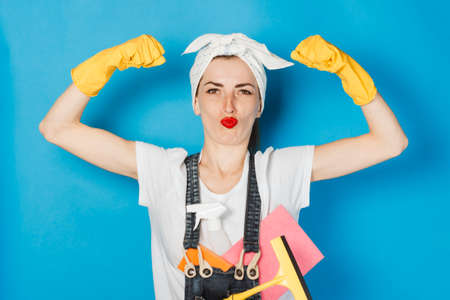 A young girl with a scarf on her head, yellow rubber gloves shows muscle biceps on her arm against a blue background. The concept of cleaning and cleaning service, high quality