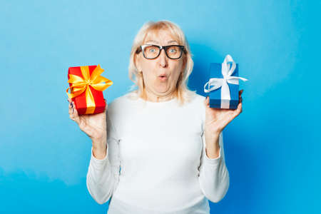 An old woman with a surprised and admired facial expression holds gifts in her hands against a blue background. Mother's Day, congratulation, birthday and holiday concept