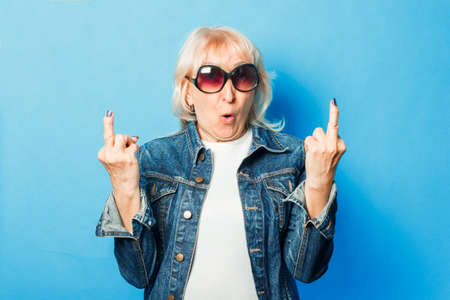 An old lady in a denim jacket, sunglasses makes an unpretentious gesture with the middle finger on a blue background. Concept fashionable grandma, old woman