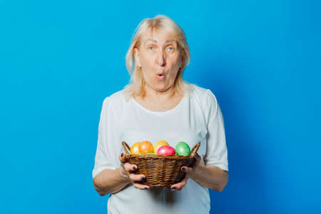 Old woman holds in her hands a basket of Easter eggs with me against a blue background. Easter celebration concept.