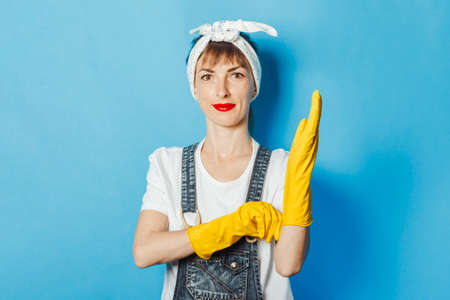 Young woman wearing yellow rubber gloves on a blue background. Cleaning concept, cleaning service, high quality.