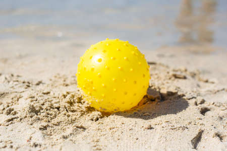 yellow ball on the sand, on the beach, children's games, travel, vacation