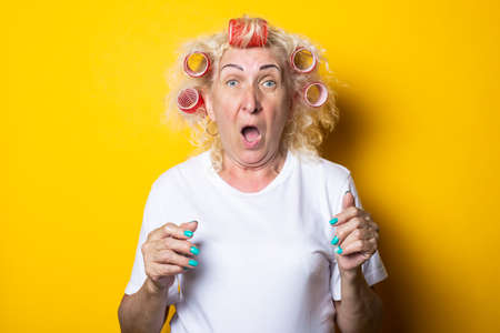 Screaming old woman with curlers in a white T-shirt on a yellow background. Stockfoto