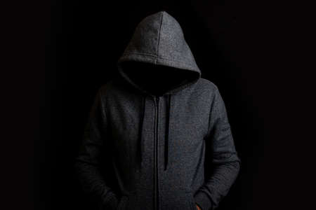 Man without a face in a hood on a dark background. Foto de archivo
