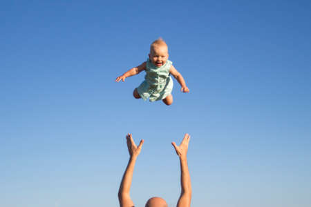 Man throws baby up against the blue sky. Concept game with children, happy family.