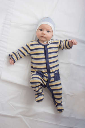 Little baby in clothes with a funny face on White sheet. Flat lay, top view.