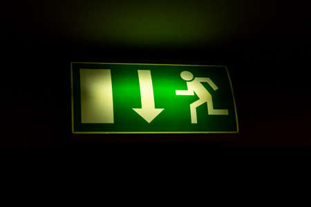 green sign indicating fire exit, arrow down straight exit on black background