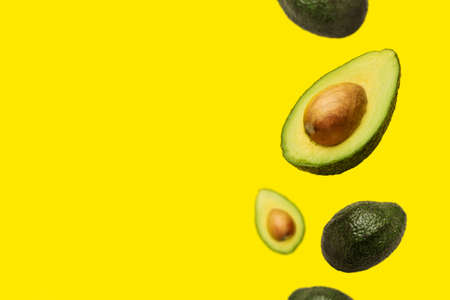 pitted avocado and whole avocado fly in the air on a yellow background. Top view, flat lay.