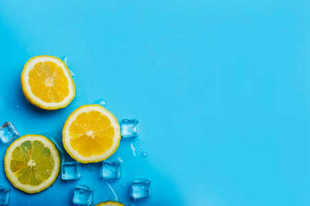 juicy fresh lemon slices and ice cubes on a blue background. Top view, flat lay. Фото со стока