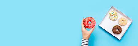 Female hand holds a donut on a blue background. Concept confectionery store, pastries, coffee shop. Banner. Flat lay, top view.