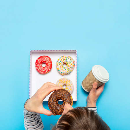 Woman eating a donut and drinking coffee on a blue background. Concept confectionery store, pastries, coffee shop. Banner. Flat lay, top view. Фото со стока