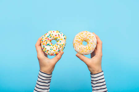 Female hands hold donuts on a blue background. Concept confectionery store, pastries, coffee shop. Banner. Flat lay, top view.