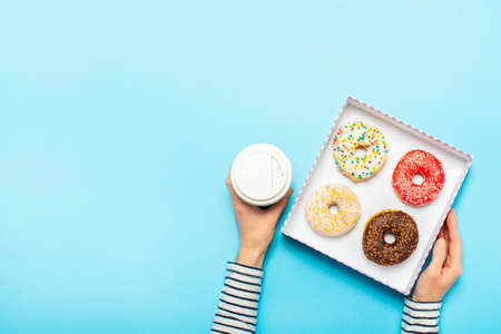 Female hands hold a box with donuts, a cup of coffee on a blue background. Concept confectionery store, pastries, coffee shop. Banner. Flat lay, top view.
