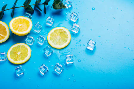 juicy yellow lemon slices, ice cubes and eucalyptus on a blue background. Top view, flat lay.
