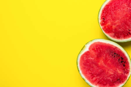 Fresh red two halves of watermelon on a bright yellow background.