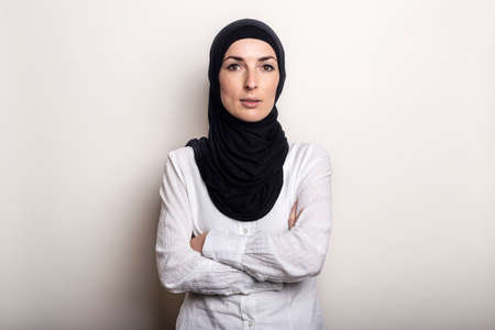 Young woman with crossed arms dressed in white shirt and hijab on light background.