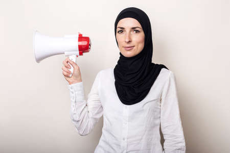 Muslim young woman in hijab holds a megaphone in her hands on a light background. Banner. Фото со стока