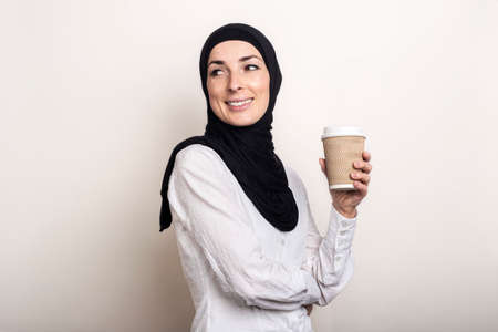 Young Muslim woman in a white shirt and hijab with a smile holds a paper cup with coffee. Banner. Фото со стока