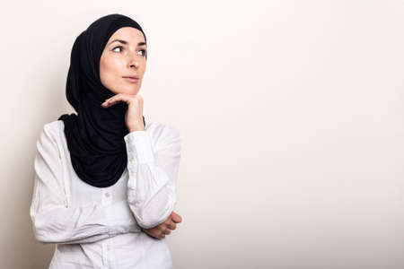 Young Muslim woman dressed in a white shirt and hijab holds her hand to her chin and looks to the side on a light background. Banner. Фото со стока