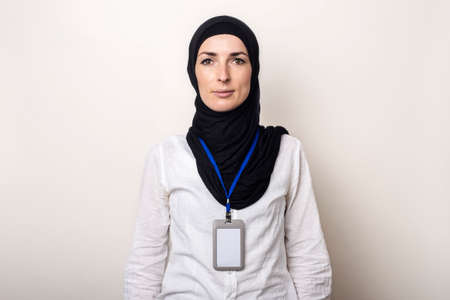 Young Muslim woman in white shirt and hijab with office badge. Work for Muslim women in the office.