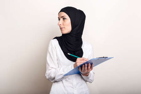 Young Muslim woman in a white shirt and hijab holds a clipboard and looks back. Auditor hiring. Banner. Фото со стока