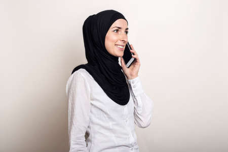 Muslim young woman in hijab talking on the phone and looking to the side on a light background. Banner.