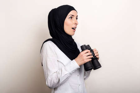 Friendly surprised Young Muslim woman in white shirt and hijab holds binoculars. Banner.