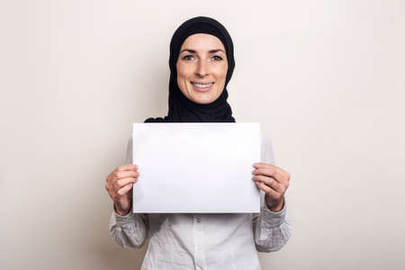 Young Muslim woman in a white shirt and hijab holds a blank sheet of paper with a smile. Place for your text. Banner. Фото со стока