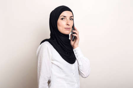 Muslim young woman in hijab talking on the phone and looking at the camera on a light background. Banner.