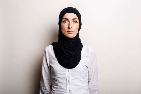 Young woman in a white shirt and hijab on a light background. Looks into the camera.