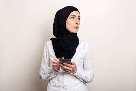 Muslim Young woman in hijab holds a phone in her hands and looks to the side on a light background. Banner.