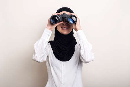 Friendly young Muslim woman in white shirt and hijab looks through binoculars. Banner. Looks into the camera. Фото со стока