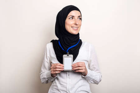 Young Muslim woman wearing white shirt and hijab showing her office badge. Work for Muslim women.