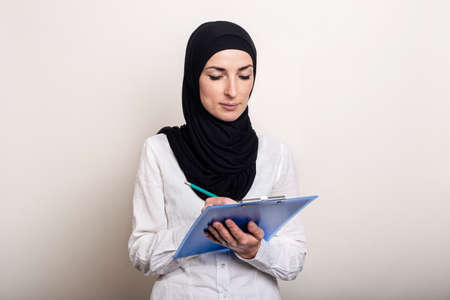 Young Muslim woman in a white shirt and hijab holds a clipboard and takes notes. Businesswoman. Banner.