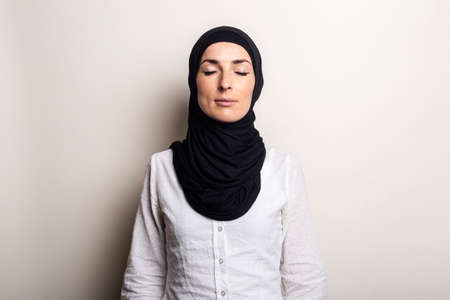 Young woman with closed eyes in white shirt and hijab on light background.