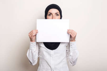 Young Muslim woman in a white shirt and hijab covers her face with a blank sheet of paper. Place for your text. Banner.
