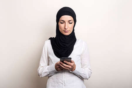 Muslim young woman in hijab holds a phone in her hands and looks into it on a light background. Banner. Writes messages.