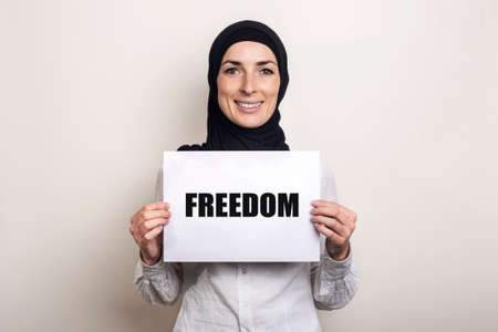 Muslim young woman with smile in hijab holds a banner with the text FREEDOM on a light background. Фото со стока