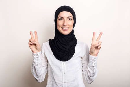 Young woman with crossed arms dressed in a white shirt and hijab shows a welcome gesture All is well on a light background. Banner.