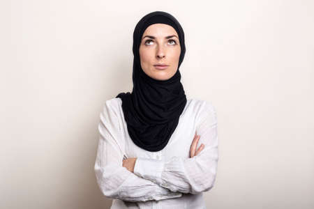 Young Muslim woman dressed in a white shirt and hijab has her arms crossed and looks up against a light background. Banner.