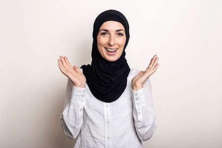 Young woman with surprised face in white shirt and hijab on light background.