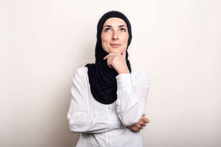 Young woman dressed in a white shirt and hijab holds her hand to her chin and looks up with a pensive face on a light background. Banner. Фото со стока