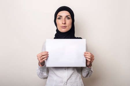 Young Muslim woman in a white shirt and hijab holds a blank sheet of paper. Place for your text. Banner.