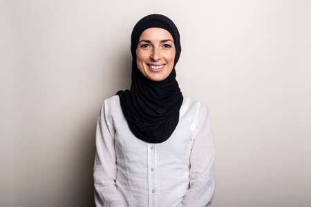 Young woman with a smile in a white shirt and hijab on a light background.